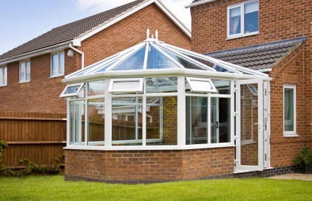 Conservatory with glass roof against a red brick house