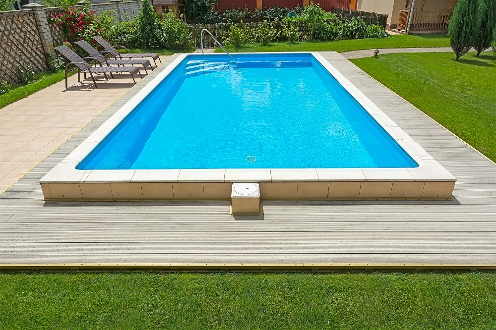 Swimming pool in the yard of a private house with a seating area and garden furniture.